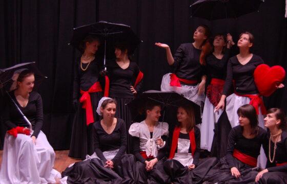Grupa dziewczyn w kostiumach pozuje na scenie do zdjęcia