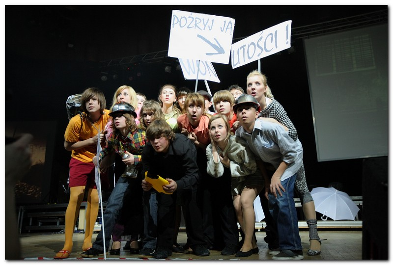 Grupa młodzieży na scenie, dziewczęta i chłopcy. Są ściśnięci. Nad nimi transparenty - litości, pożryj ją, won.