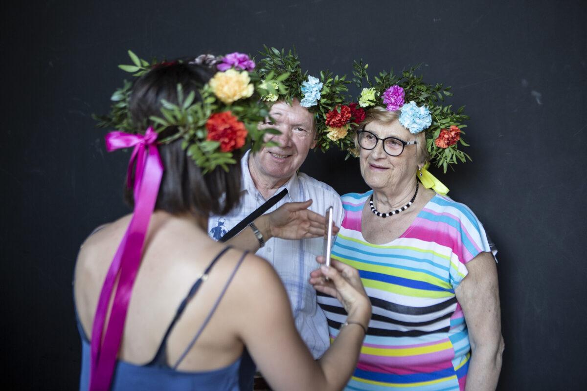 Starszy mężczyzna i starsza kobieta. Oboje uśmiechnięci na przeciwko nich, tyłem do obiektywu kobieta. Wszyscy mają kwiatowe wianki na głowie.