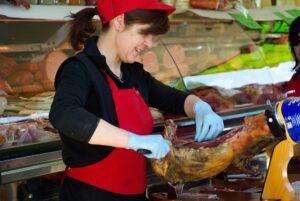 Młoda kobieta przed ladą z wędlinami i mięsem kroi plastry mięsa