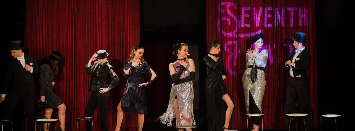 Osiem młodych osób na scenie w kostiumach z lat dwudziestych ubiegłego wieku. Za nimi napis Seventh Heaven