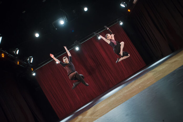 Młoda dziewczyna i młodyy chłopak uchwycenie w wysokim podskoku na scenie