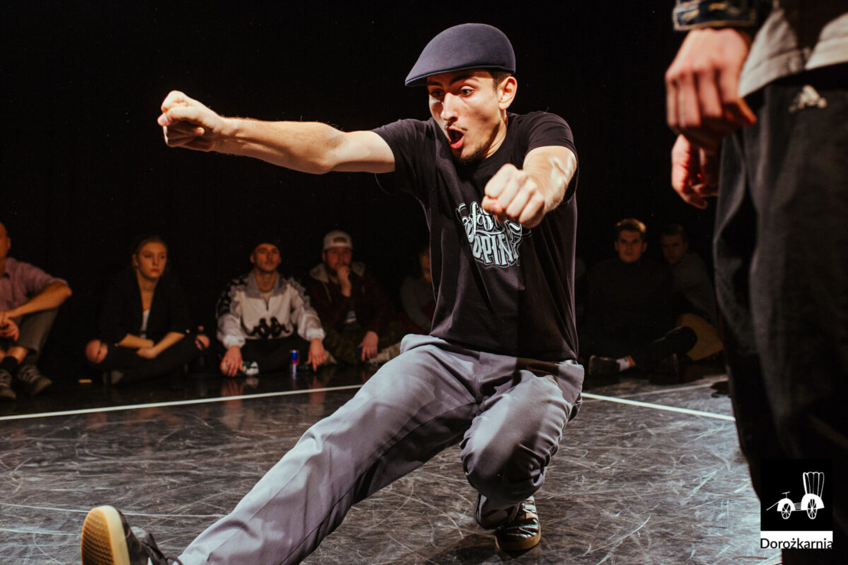 Młody chłopak na tańczy, najprawdopodobniej breakdance. Wokół niego tłum młodych ludzi.