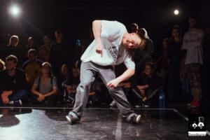 Młody chłopak w czapce z daszkiem tańczy prawdopodobnie popping, wokół niego młodzi ludzie siedzą na podłodze