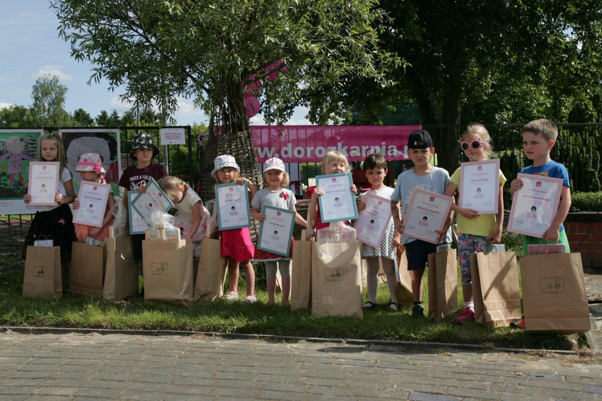 Grupa dzieci w wieku przedszkolnym z dyplomami w dłoniach i dużymi torbami papierowymi. Zdjęcie zrobione na podwórku