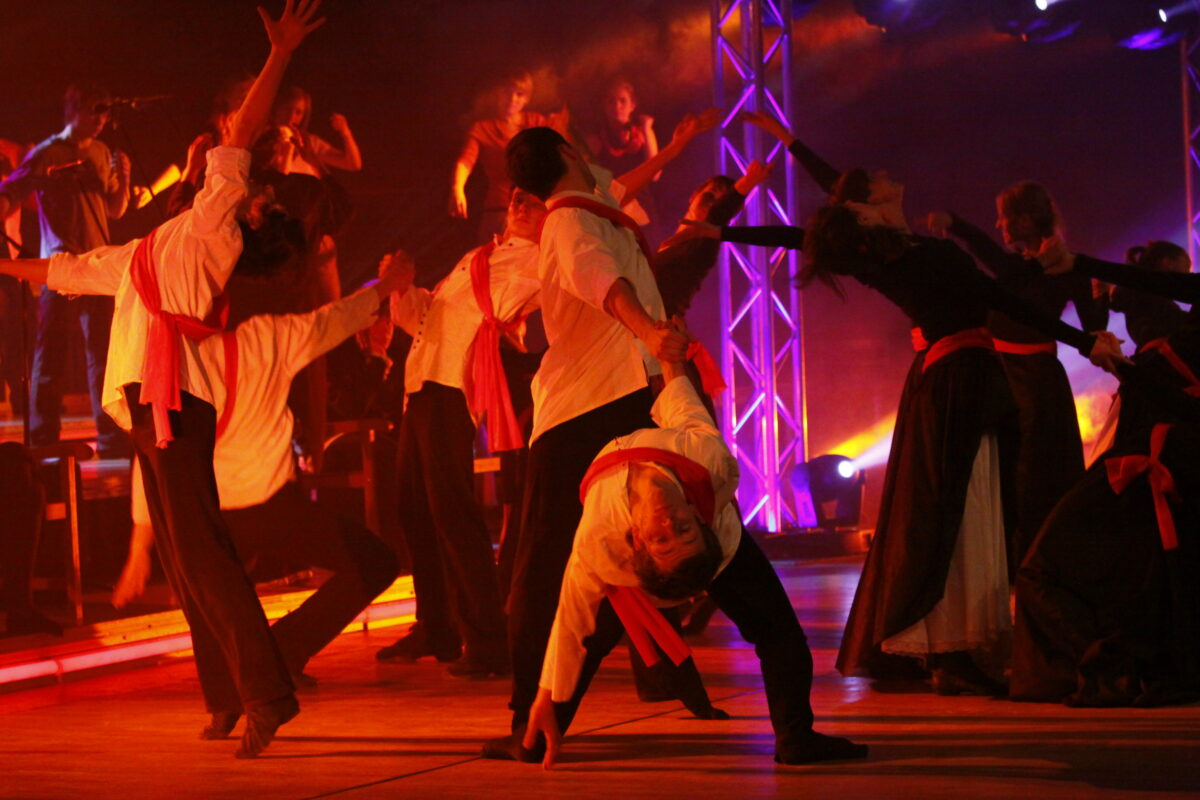 Zdjęcie ze spektaklu - na scenie grupa młodzieży dziewcząt i chłopców w dziwnych pozach. Dziewczyny w sukienkach do ziemi, chłopcy na koszulach mają szarfy.