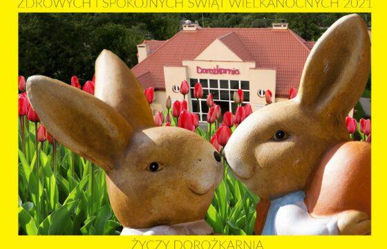 Kartka wielkanocna, na pierwszym planie dwa króliki z ciasta, w tle tulipany i budynek z neonem Dorozkarnia