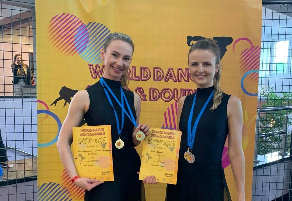 Dwie uśmiechnięte dziwczyny trzymają w dłoniach dyplomy, na piersiach mają po 2 medale