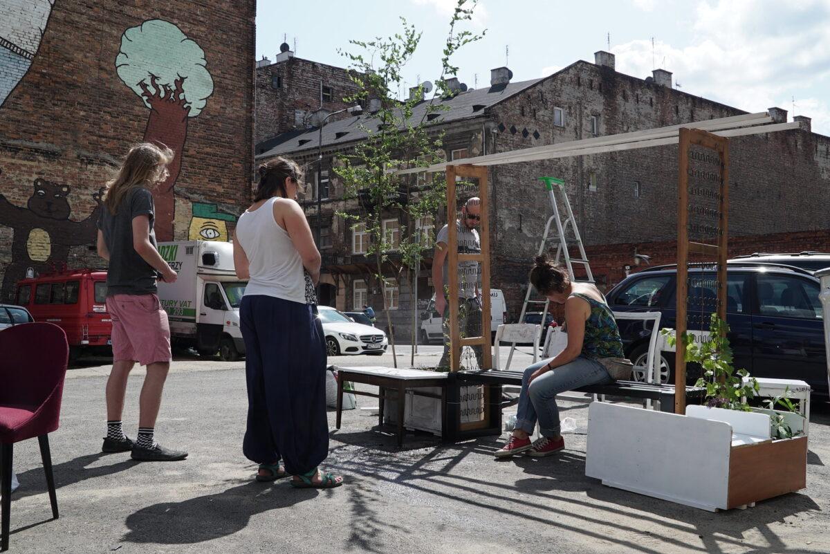 Zdjęcie wykonane latem na podwórku, wśród starych kamienic. W centrum zdjęcia na ławce siedzi kobieta, patrzą na nią dwie osoby, za ławką idzie mężczyzna.