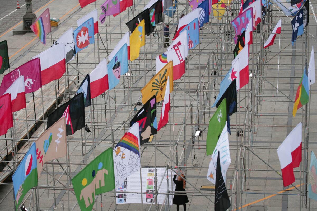 Kilkanaście flag na masztach,. Maszty stoją jeden obok drugiego. Zdjęcie zrobione jest z góry