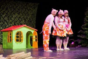 Trzy postacie na scenie w kostiumach świnek, za nimi mały domek
