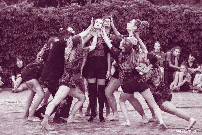 Grupa młodzieży na scenie pelenerowej, prawdopodobnie tancerzy. W centrum stoi chłopak, wokół niego dziewczyny. Wszyscy ubrudzeni gliną
