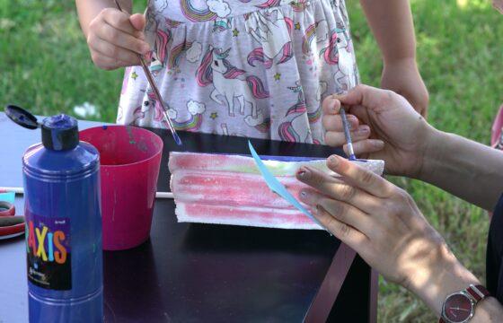 Widzimy fragment stołu, na nim obrazek, dłonie osoby dorosłej i dziecięce z pędzelkami, naczynie z wodą, pojemnik z farbą