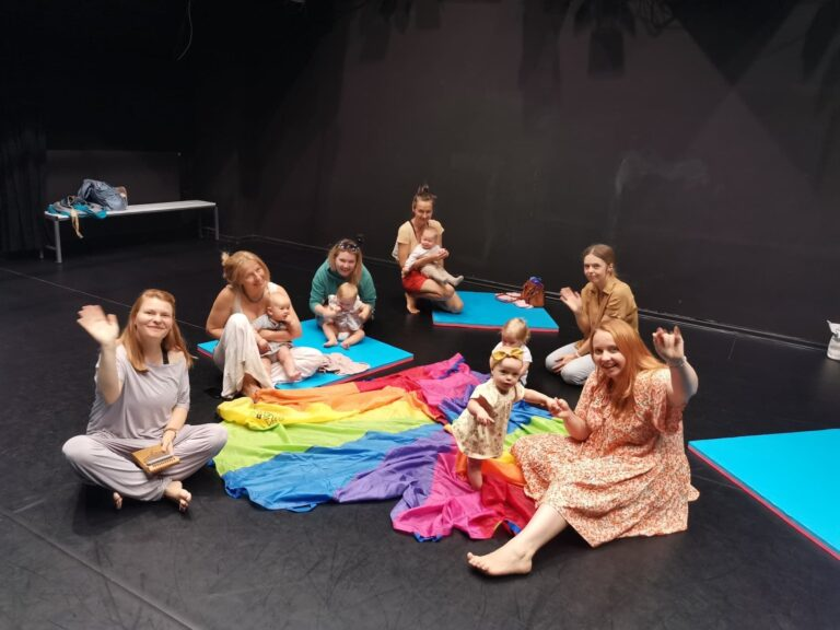 Grupa kobiet z małymi dziećmi, siedzą na podłodze w pomieszczeniu, machają do fotografa