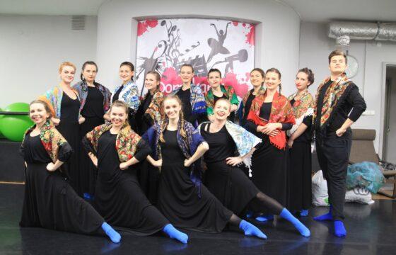 Zdjęcie grupowe zespołu tanecznego. Wszyscy ubrani są w czarne sukienki i spodnie, na stopach wszyscy mają intensywnie niebieskie skarpetki. Na ramionach wszyscy mają kolorowe, ludowe chusty.