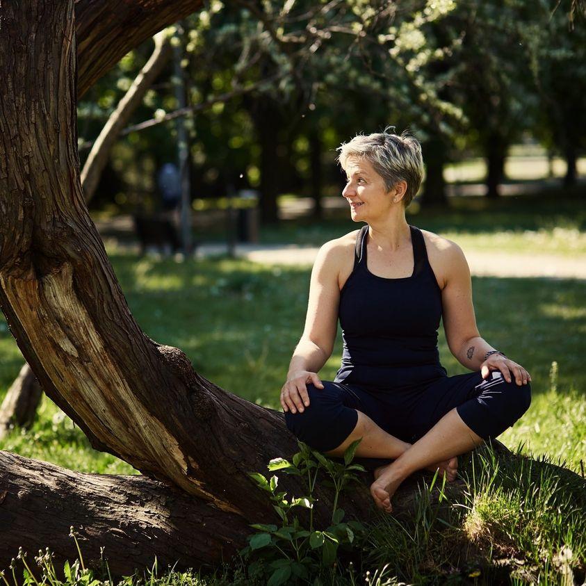 Kobieta w stroju do jogi siedzi po turecku w plenerze