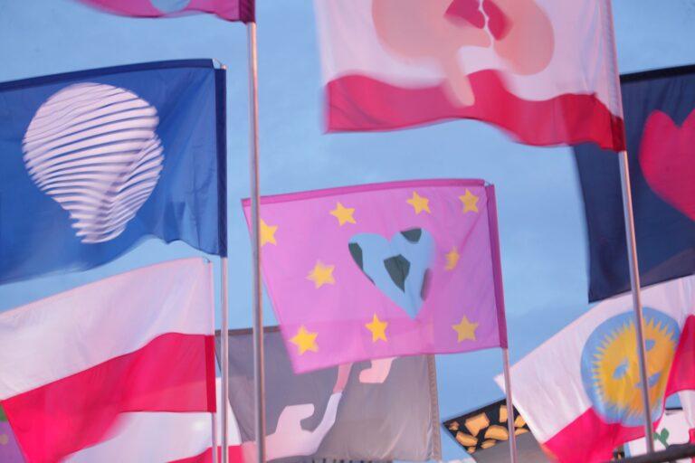Zdjęcie przedstawia różnorodne flagi na tle nieba.