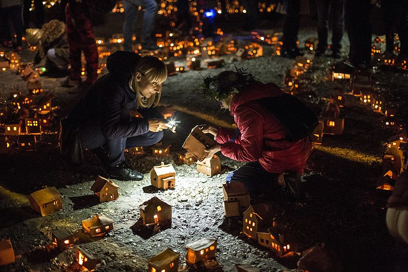 Miniaturowe gliniane domki. Jest ich bardzo dużo. Rozstawione są na ziemi na dużej przestrzeni, wewnątrz nich palą się malutkie świeczki. Pośród nich wędrują ludzie