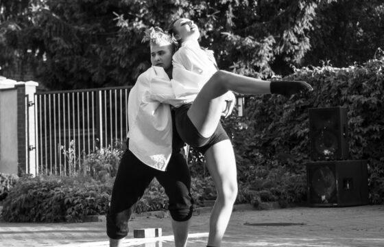 Młoda dziewczyna i młody chłopak tańczą. Chłopak podnosi dziewczynę. Za nimi widać fragment płotu, drzewa, krzewy