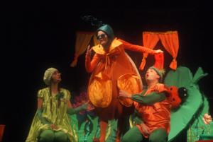 Zdjęcie przedstawia scenę z bajki dla dzieci - trzy postacie w kostiumach warzyw.