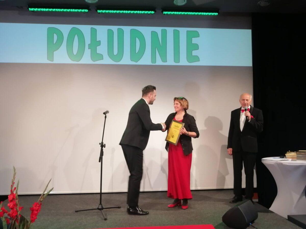 Trzy osoby na scenie. Od lewej młody mężczyzna śiska dłoń uśmiechniętej kobiety. Z prawej mężczyzna z mikrofonem w dłoni.