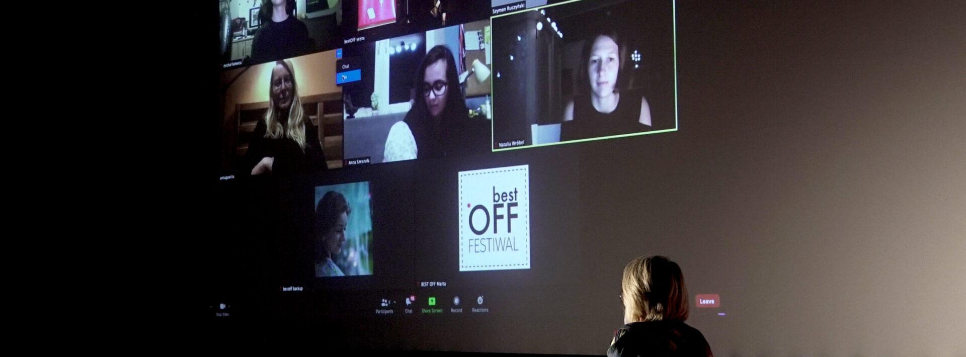 Zdjęcie z festiwalu Best off 2020. Na zdjęciu widać obraz z wideokonferencji na kinowym ekranie. Osiem okienek w których są widoczne głowy twórców filmów. w jednym z okienek napis best off festiwal. w prawym dolnym rogu zdjcia tyłem siedzi kobieta w blond włosach i kolorowej kurtce. kobieta rozmawia z uczestnikami wideokonferencji