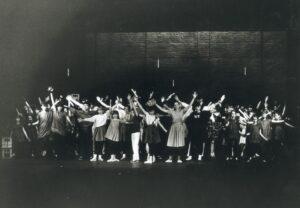 Duża grupa młodzieży na scenie, stoją w różnych pozach z rękami wyrzuconymi do góry