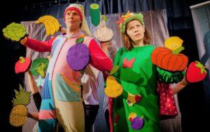 Kobieta i mężczyzna w kostiumach scenicznych z bajki dla dzieci, do kostiumów mają przyszyte materiałowe owoce i warzywa, m. in.: dynię, paprykę, ananasa, gruszkę