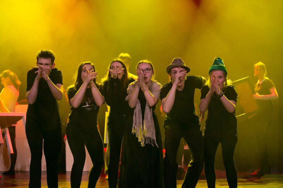 Zdjęcie przedstawia sześć młodych osób na scenie - cztery dziewczyny i dwóch chłopaków, stoją blisko siebie, dłonie trzymają przy twarzy
