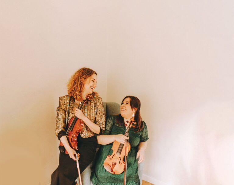 dwie młode konbiety ze skrzypcami w dłoniach, uśmiechają się, patrzą na siebie