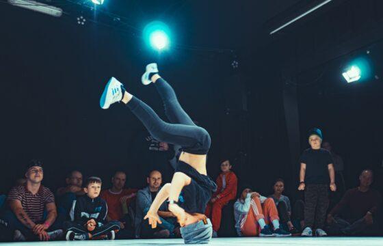Chłopak na scenie - tańczy breakdance, na głowie. Za nim siedzą widzowie