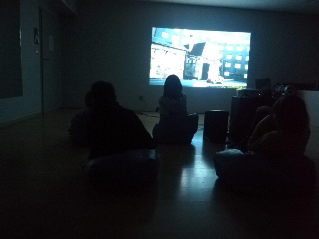 zdjęcie przedstawia cztery osoby siedzące w ciemności. na dalekim planie widać kadr z filmu wyświetlony z rzutnika na ścianie. światło świecące z obrazu oświetla postaci.
